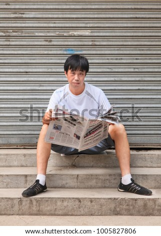 BEIJING-AUGUST 10, 2010. A Chinese man reading a newspaper sitting on a small staircase. China has the largest newspaper market in the world, with 1,937 newspapers printing 43.9 billion copies