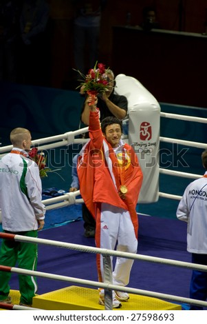BEIJING - AUGUST 24: Chinese Olympic light flyweight boxer Zou Shiming holds up China's first ever gold medal in boxing August 24, 2008 in Beijing, China.