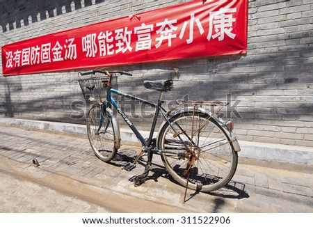 BEIJING-AUGUST 10, 2015. Red banner with a slogan on a brick wall in Beijing hutong. The Beijing municipal government is campaigning with huge red banners to teach its citizens communist values. - stock photo