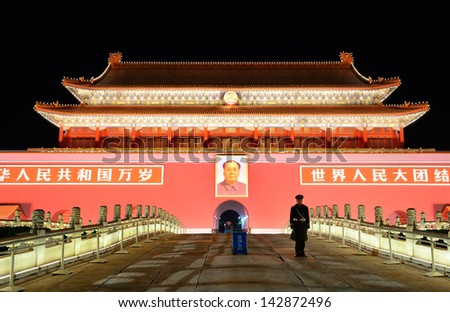 BEIJING, CHINA - APR 1: Tiananmen exterior with guard at night on April 1, 2013 in Beijing, China. It is a famous monument in Beijing and serves as a national symbol. - stock photo
