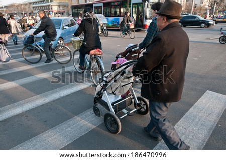 BEIJING, CHINA - APRIL 1: Chinese people walks on pedestrian crossing on April 1, 2013 in Beijing - stock photo