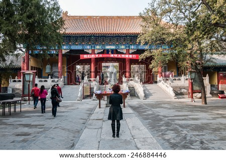 BEIJING, CHINA - APRIL 3: Chinese tourists in front of statue of Confucius in The Temple of Confucius on Guozijian Street on April 3, 2013 in Beijing - stock photo