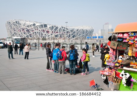 BEIJING, CHINA - APRIL 2: Tourists stand next to souvenir kiosk near National Stadium in Chaoyang District, commonly known as Bird's Nest on April 2, 2013 in Beijing - stock photo