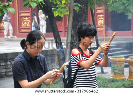 BEIJING, CHINA, AUG 29: Two Young Chinese women (one is in motion) holding incense sticks at the Lama Temple, Beijing, China, Aug 29, 2014 - stock photo