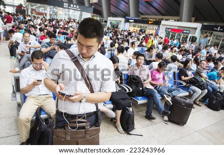Beijing, China - August 6, 2014: People are waiting for a train at an overcrowded railway station in Beijing. - stock photo