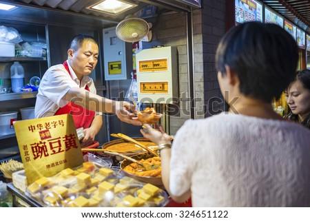 Beijing, China -  August 18, 2015: Seller selling Ancient Beijing sweet pease pudding (Beijing Wandouhuang), Beijing Snacks. Located in Wangfujing Snack Street. Beijing, China. - stock photo