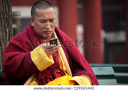 BEIJING, CHINA - CIRCA JANUARY 2013: Unidentified Monk using phone in the Lama Temple on circa January 2013 in Beijing, China. It is one of the largest and most important Tibetan Buddhist monasteries in the world. - stock photo