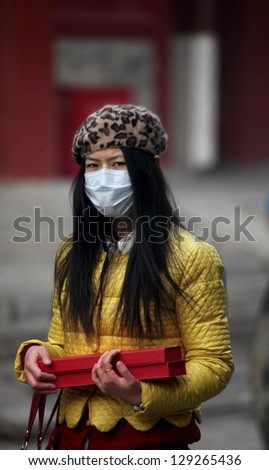 BEIJING, CHINA - CIRCA JANUARY 2013. Unidentified woman with mask in the Lama Temple on circa January 2013 in Beijing, China. It is one of the largest and most important Tibetan Buddhist monasteries in the world. - stock photo