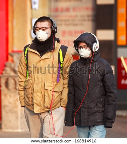 BEIJING, CHINA-DEC 25, 213: People is seen with face mask; a high-ranking environmental official has estimated cleaning up China's air pollution will cost 1.75 trillion yuan between 2013 and 2017 - stock photo
