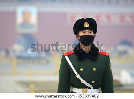 BEIJING, CHINA - DECEMBER 20, 2015: A Chinese military man wears a face mask at Tiananmen Square. Beijing issued a red alert for air pollution on Friday, its second red alert this month.