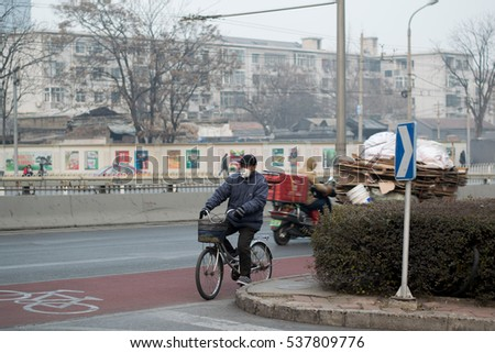 BEIJING, CHINA - DECEMBER 17, 2016: An unidentified man rides a bicycle during air pollution in Beijing. Air pollution is a serious problem in Beijing.