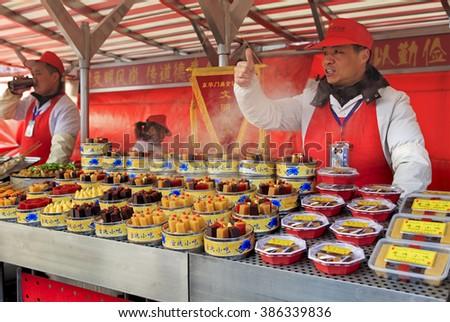 BEIJING, CHINA-FEBRUARY 21, 2016: A food vendors offer Beijing local desserts  at Donghuamen Night Market near Wangfujing Street. Wangfujing is a 700-year-old commercial street - stock photo