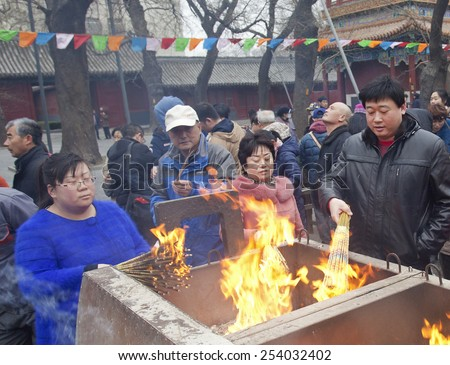 BEIJING, CHINA - FEBRUARY 19, 2015: People burn incense at Yonghegong Lama Temple on the first day of the Chinese Lunar New Year, the year of the sheep, which started on February 19 this year.   - stock photo