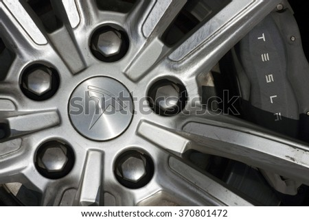 BEIJING, CHINA - JANUARY 31, 2016: Close-up of the wheel of a Tesla electric car in the streets of Beijing, China on January 31, 2016.