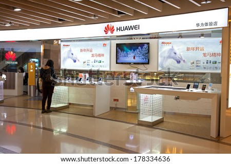 BEIJING, CHINA - JANUARY 2, 2014: People in seen at a Huawei store; Huawei, a Chinese multinational company, is the largest telecommunications equipment maker in the world. - stock photo