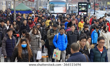 BEIJING, CHINA - JANUARY 10, 2016: Unidentified people are seen around Wangfujing street. Wangfujing is a 700-year-old commercial street; itâ??s about 810 meters long and 40 meters wide. - stock photo