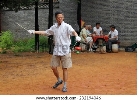 BEIJING, CHINA - JUL 17, 2011: Chinese man training with some kind of yo-yo in Jingshan park, not far from Forbidden City. Chinese yo-yo (kongzhong or hollow bell) was found during the Ming dynasty