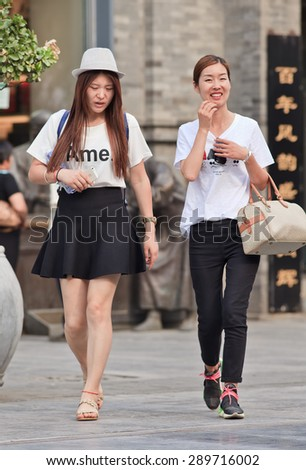 BEIJING, CHINA -JUNE 9, 2015. Fashionable young women at Qian Men. First generation one-child policy consumers have opposite shopping habits from parents. They barely save and spend income rather on fashion. - stock photo