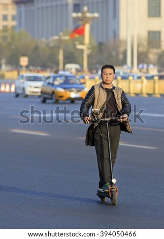 BEIJING, CHINA - MARCH 20, 2016: An unidentified man rides an electric scooter near Tiananmen square. Beijing government's  plans to include more bike lanes to help reduce city smog. - stock photo