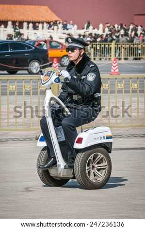 BEIJING, CHINA - MARCH 28: Chinese police officer on segway personal transporter G3 Cargo made by Freeyoyo  company on Tiananmen Square on March 28, 2013 in Beijing - stock photo