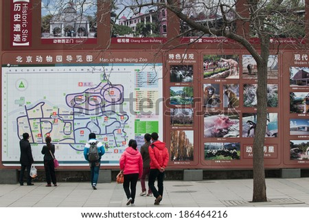 BEIJING, CHINA - MARCH 29: Chinese tourists stands in front of large information board in Beijing Zoo on March 29, 2013 in Beijing - stock photo