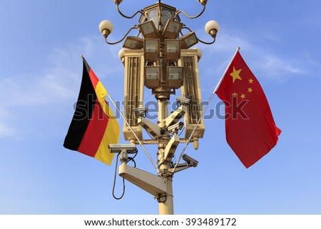 BEIJING, CHINA - MARCH 20, 2016: German and Chinese National flags flutter on a lamppost at Tiananmen Gate during the visit of German President Joachim Gauck in China. - stock photo