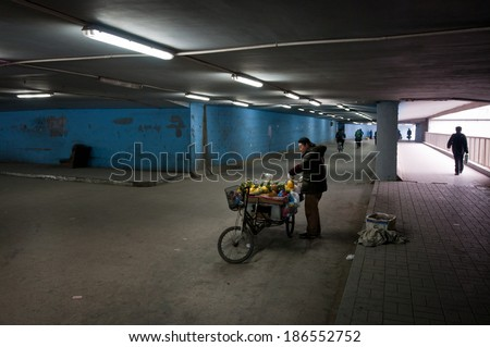 BEIJING, CHINA - MARCH 29: Man sells carved pineapples in underground passage on March 29, 2013 in Beijing - stock photo