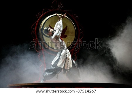 BEIJING, CHINA - NOVEMBER 16: A drummer performs the 'whipping drum' show on a giant drum on November 16, 2005 in Beijing, China. This dance is performed during major festivities in rural China. - stock photo