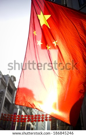 BEIJING, CHINA - OCT 1: National flag is flying in the sky near Tiananmen square on the National Day on October 1, 2013 in Beijing, China. - stock photo