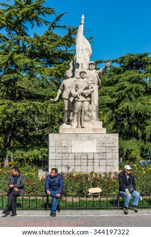 BEIJING, CHINA - OCTOBER 15, 2013: Chinese Men relaxing in the front of revolutionary statue in Dongdan Park in DongCheng District, Beijing, China - stock photo