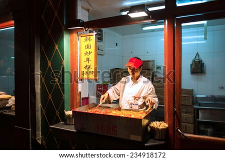 BEIJING, CHINA - OCTOBER 24, 2014: Wangfujing Snack Street at night. Chinese chef making tradition Korean fried rice cake. Located in Beijing, China.