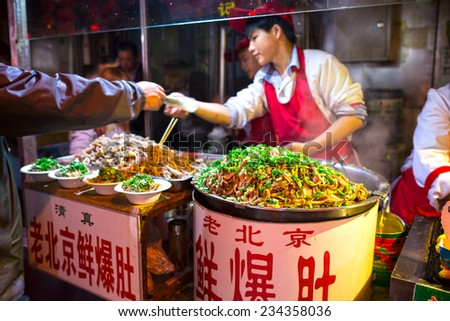 BEIJING, CHINA - OCTOBER 24, 2014: Wangfujing Snack Street at night. Chinese chef selling Ancient Beijing Soiled Pork Tripe. Located in Beijing, China. - stock photo