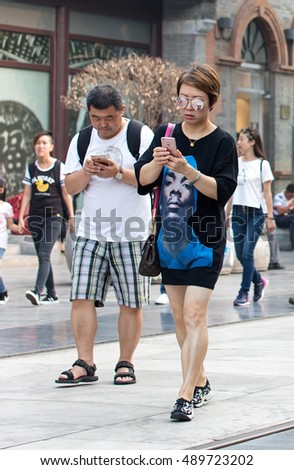 BEIJING, CHINA - SEPTEMBER 16, 2016:  Unidentified people are seen using Apple mobile phones at Qianmen Street. Apple's iPhone 7 goes on sale in mainland China from September 16.