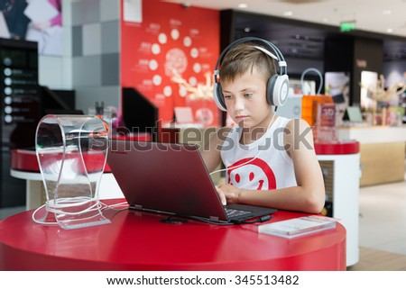 BEIJING - CIRCA JUNE, 2015: Boy with headphones using a laptop in the Lenovo store is on a Qianmen street in the center of  Beijing. Lenovo Group Limited - world-famous Chinese computer company. - stock photo