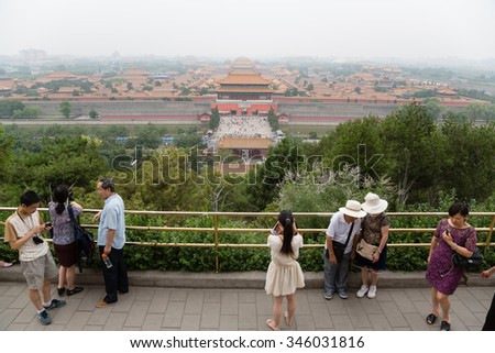 BEIJING - CIRCA JUNE , 2015: Tourists on a viewing platform in the Jingshan park. Observation desk Jingshan Park is the highest point of the old Beijing, it offers view of the Imperial Forbidden City - stock photo