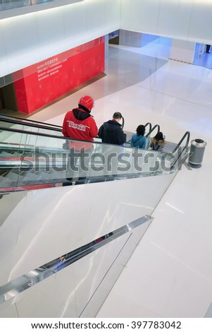 BEIJING-DEC. 5, 2015. People on escalator in shopping mall. Chinese people are reluctant take escalators after a woman became trapped following the sudden collapse of an escalator at a shopping mall.  - stock photo