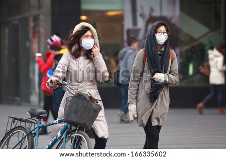 BEIJING-DEC 8: People with face masks are seen on Dec 8,2013 in Beijing, China.  104 cities in China suffered from severe air pollution on Dec7, Beijing was among that hit the hardest - stock photo