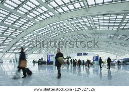 BEIJING-FEB. 21. Passengers at railway station, Beijing Capital Airport Terminal 3. The world's largest airport terminal-building complex measures 986,000 m2 floor surface. Beijing, Feb. 21, 2013. - stock photo