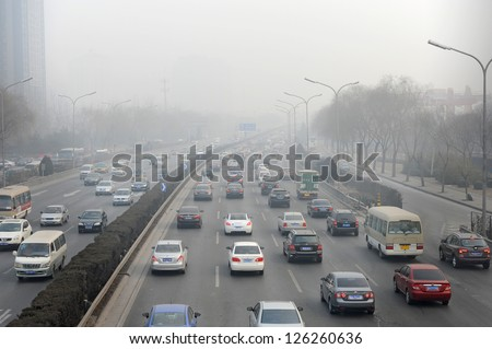 """BEIJING - JAN 12: traffic jam and severe pollution on January 12, 2013 in Beijing, China.   Air quality index levels were classed as """"Beyond Index"""" (PM 2.5 of over 700 micrograms per cubic meter). - stock photo"""