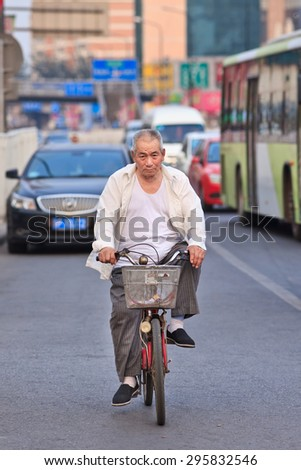 BEIJING-JULY 10, 2015. Chinese senior on a bicycle. Although the fast multiplication of cars in China the bicycle remains the biggest means of individual mobility for hundreds of millions Chinese. - stock photo