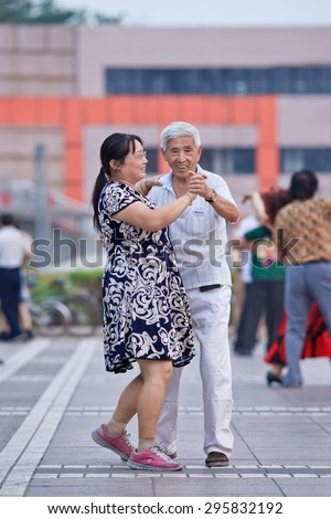 BEIJING-JULY 10, 2015. Collective square dancing. Its vast popularity has also a drawback, due to the nuisance the Chinese government will launch soon national standards and regulations to guide it. - stock photo
