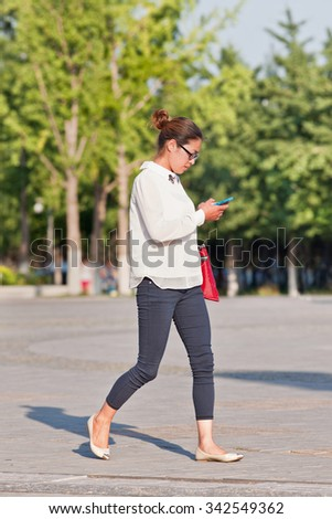 BEIJING-JULY 3, 2015. Fashionable attractive young woman with smartphone. China has currently 519.7 million smartphone users. That figure will rise to 574.2 million Chinese smartphone users by 2015. - stock photo