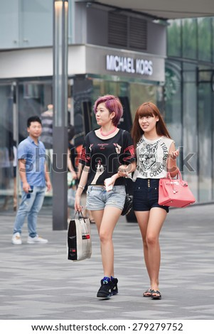 BEIJING-JULY 25, 2014. Fashionable girls at The Village shopping area.  For the past decade, China's economic boom has dominated global fashion. Leading brands began to see the potential of China. - stock photo