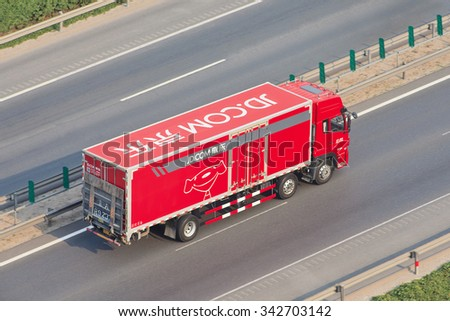 BEIJING-JULY 7, 2015. JD.Com truck on the expressway. JD.com or Jingdong Mall is a Chinese electronic commerce company which is one of the largest B2C online retailers in China by transaction volume. - stock photo