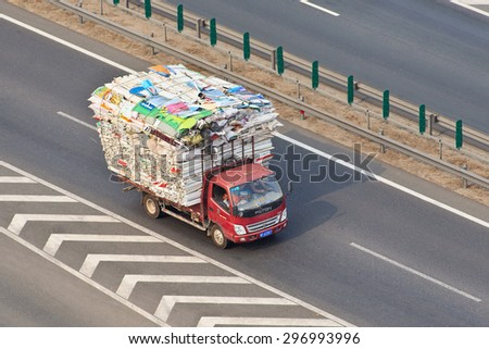 BEIJING-JULY 10, 2015. Overloaded small truck on the expressway. Although China has strict traffic laws and regulations overloading is raised to culture due to the lack of efficient law enforcement. - stock photo