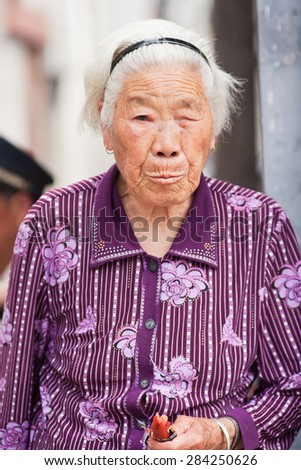 BEIJING-JUNE 1, 2015. White haired old women. Elderly population (60 or older) in China is about 128 million, one in every ten people, the world's largest. China will have 400 million elderly by 2050. - stock photo