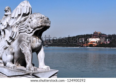 BEIJING - MAR 14:Marble Chinese lion sculpture against the Summer Palace on Kunming Lake  on March 14 2009. The Summer Palace is the best preserved imperial garden in the world. - stock photo
