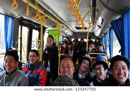 BEIJING - MARCH 10:Happy  Chinese people in a bus on the way to the Great Wall of China on MARCH 10 2008 near Beijing ,China.Four million people visits the great wall each year. - stock photo