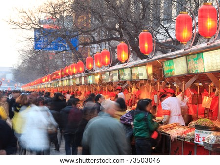 BEIJING - MARCH 17: Many Visitors and local are seen around a Wangfujing snack street on March 17, 2011 in Beijing, China. Exotic snacks and desserts can be found in this famous market. - stock photo