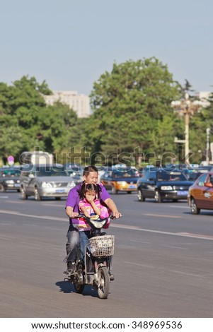 BEIJING-MAY 29, 2013. Father and daughter on e-bike. In a decade, e-bikes in China climbed from near zero to over 150 million, largest adoption of alternative fuel vehicle in history of motorization. - stock photo